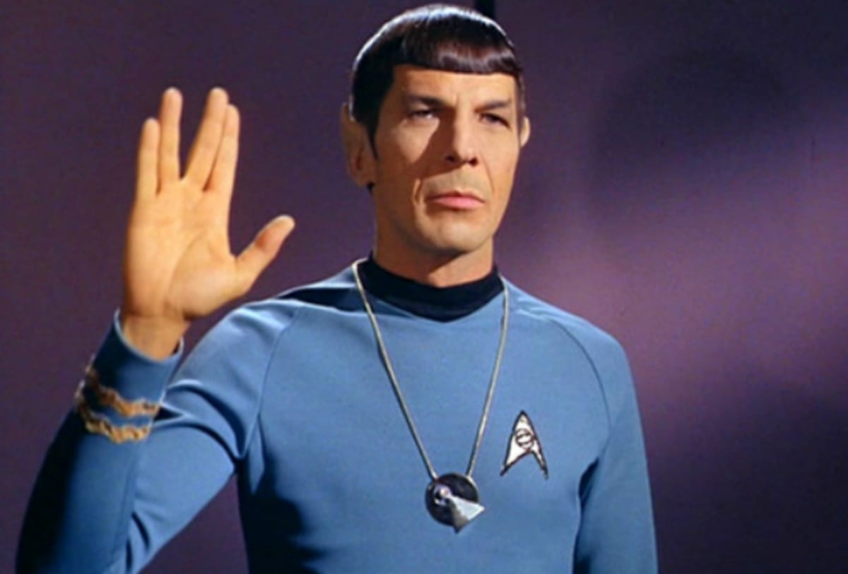 Spock wearing IDIC symbol giving Vulcan salute.